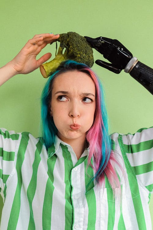 Woman in White and Green Stripe Button-Up Shirt Holding Brocolli on Her Head