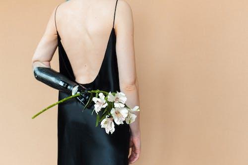 Woman in Black Spaghetti Strap Dress Holding White Flowers