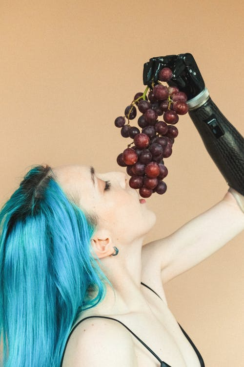 Woman With Blue Hair Holding Grapes over Her Mouth