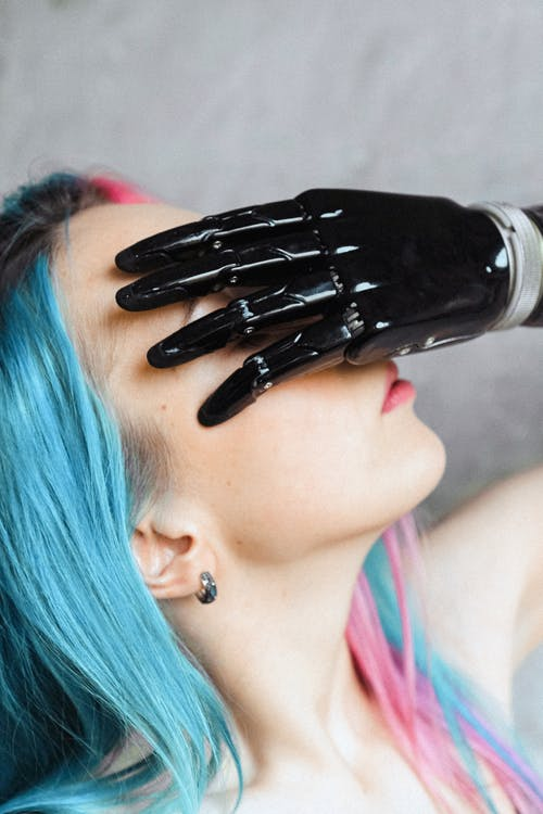 Woman with Colored Hair Covering Her face with Hand
