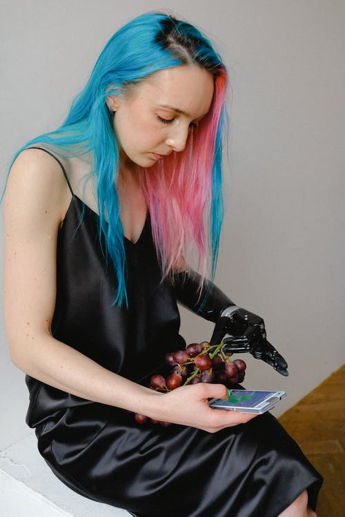 Woman in Black Slip Dress Holding Bunch of Grapes and Smartphone