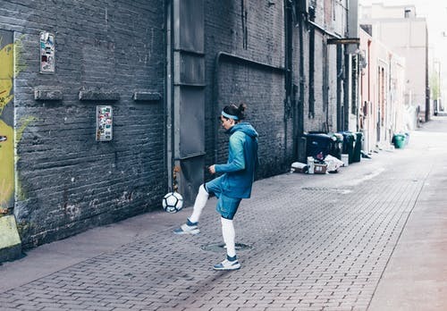 Man in Blue Jacket and Blue Denim Jeans Playing Football on the Alley