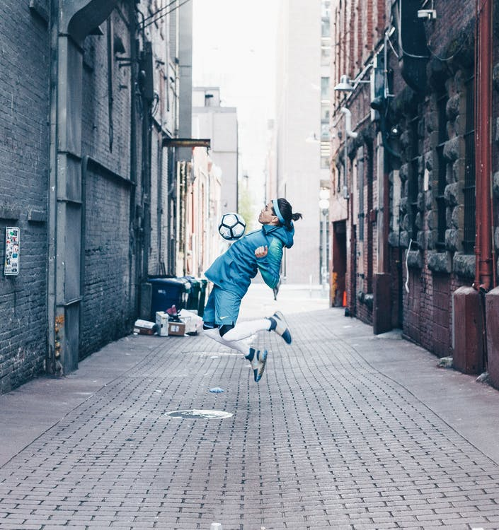 Side view of male footballer in moment of playing with ball on narrow street in city