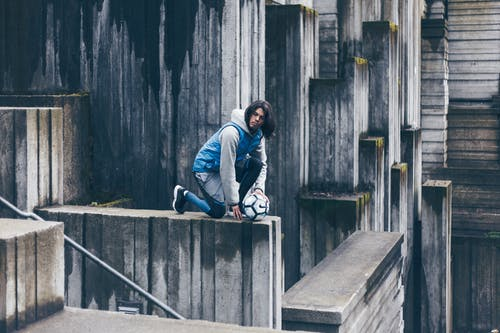 Man in Blue Denim Jacket Sitting on Concrete Stairs