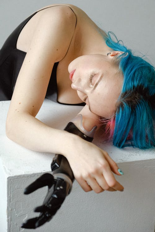 Woman in Black Sleeveless Top Lying on White Table