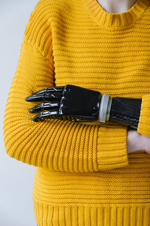Person in Yellow Knit Sweater in a Prosthetic Arm