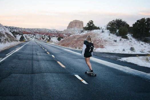 Woman in Black and White Long Sleeve Shirt Riding a Skateboard on a Freeway Road