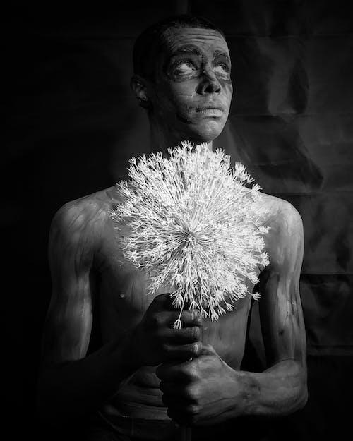 Grayscale Photo of Man Holding Dandelion