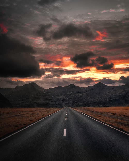 Black Asphalt Road Near Mountains Under Cloudy Sky