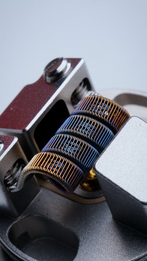 Closeup of fused clapton coil on dripper of modern electronic cigarette on white background