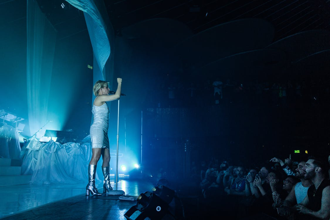 Woman in White T-shirt and White Shorts Standing on Stage
