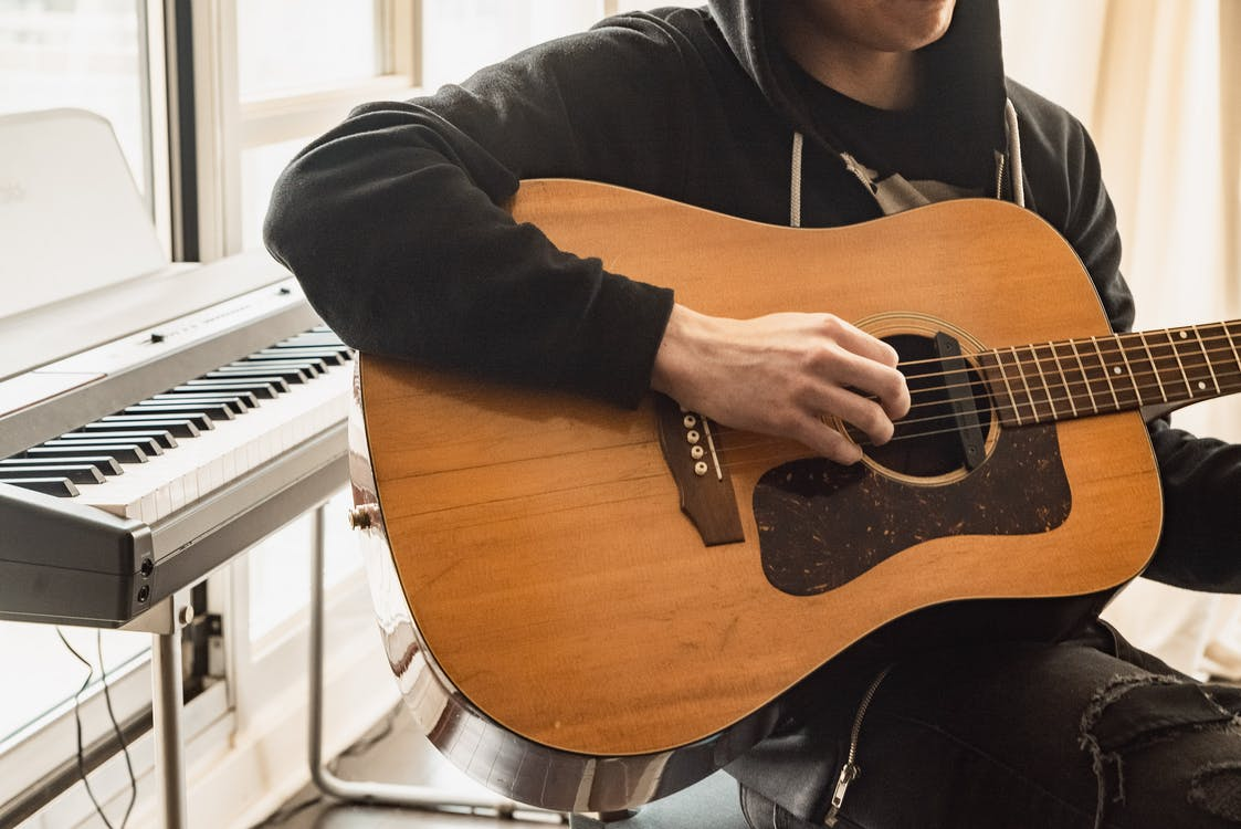 Person in Black Long Sleeve Shirt Playing Brown Acoustic Guitar
