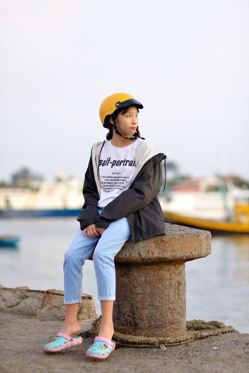 Girl in Grey Hoodie and Yellow Cap Sitting on Brown Concrete Bench Near Body of Water