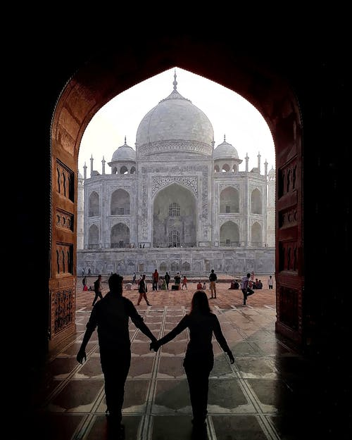 Back view of silhouette of loving traveling couple holding hands and walking through arch towards Taj Mahal