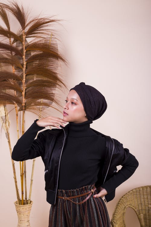 Woman in Black Hoodie Standing Near White Wall