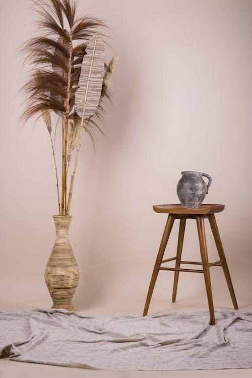 Brown Plant in Blue Ceramic Vase on Brown Wooden Stool