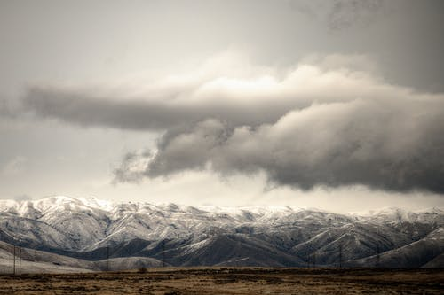 Breathtaking landscape of rough mountain range covered with snow on background of thunderstorm sky in winter