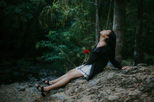 Woman in Black Long Sleeve Shirt Sitting on Rock