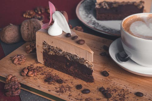 Chocolate Cake On Wooden Board Next to Cup of Coffee