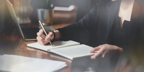 Photo Of Person Writing On White Paper