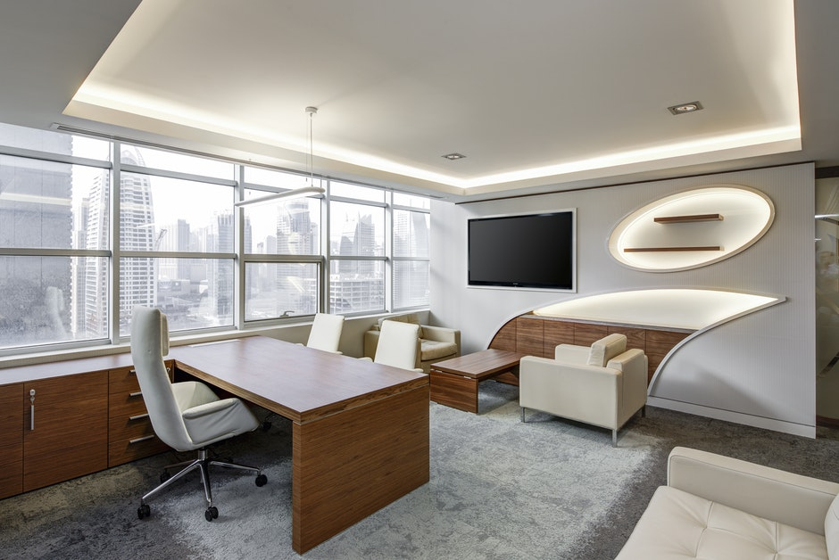 Gray Office Rolling Chair Near Brown Wooden Desk in Front of Flat Screen Tv on White Painted Wall