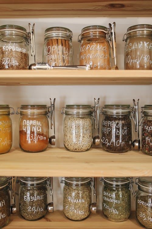 Variety of Spices in Glass Jars on Wooden Shelves