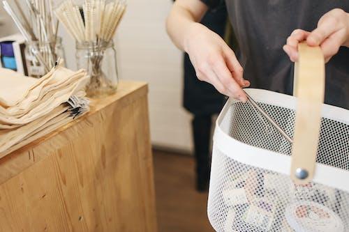 Person Holding White Plastic Basket