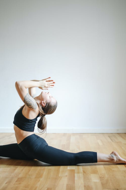 Woman in Black Tank Top and Black Leggings Doing Yoga on the Floor