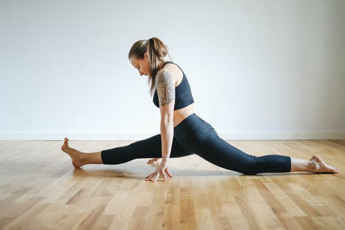 Woman in Black Sports Bra and Black Leggings Doing Yoga on Brown Wooden Floor