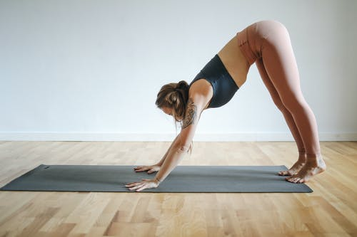 Woman in Black Sports Bra and Brown Leggings Doing Yoga on Yoga Mat on Brown Wooden Floor