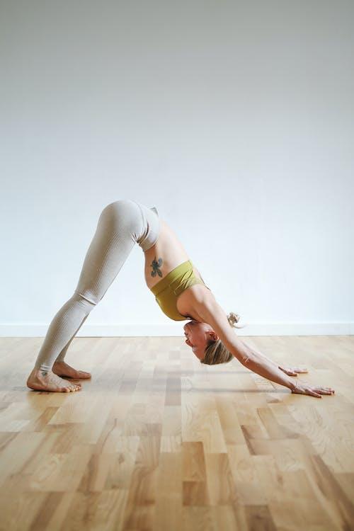 Woman in Green Sports Bra and White Leggings Doing Yoga