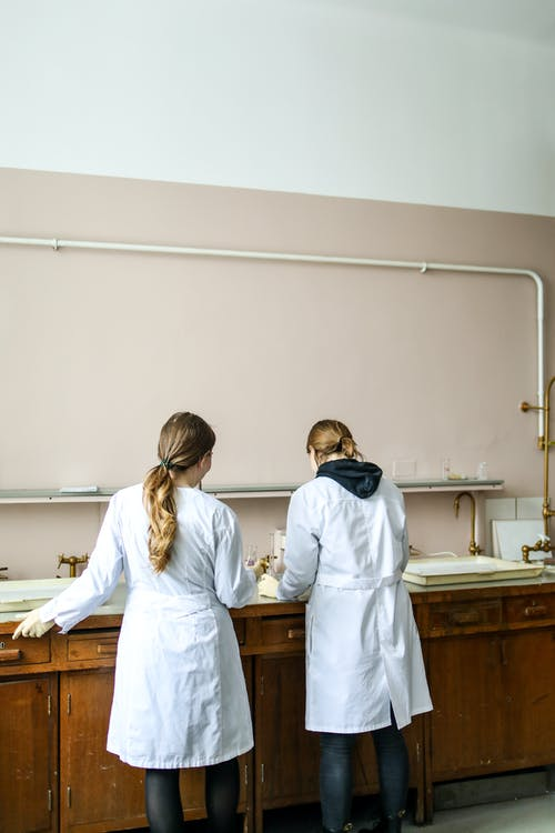 Women In White Laboratory Gown Standing In Front Of A Counter