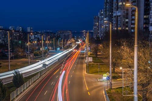 Timelapse Photography of Vehicle Passing by Buildings