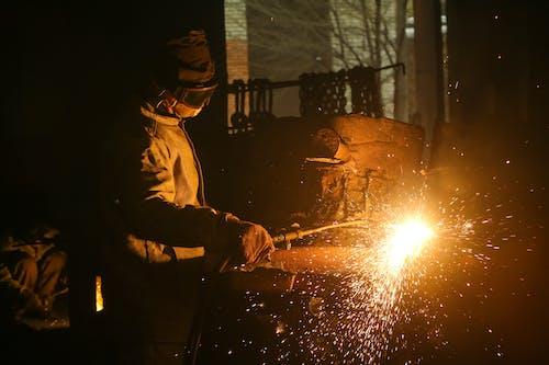 Male employee working with welding machine