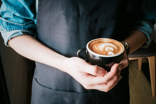 Woman Holding Mug of Cappuccino