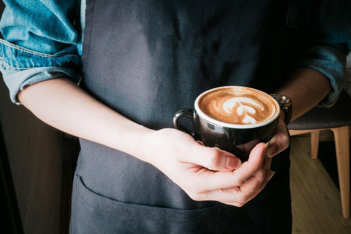 Woman Holding Mug of Cappuccino