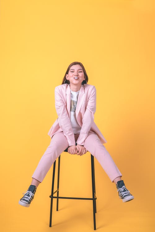 Woman in Pink Suit Sitting on Stool