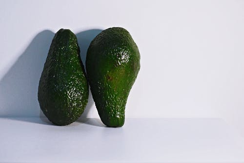Two Green Avocados on White Surface