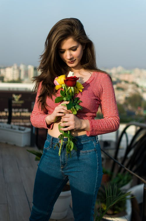 Woman in Red and White Striped Top Holding a Bunch of  Roses