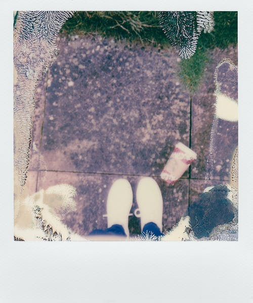 Polaroid Shot of Person Standing on Concrete Floor in White Sneakers