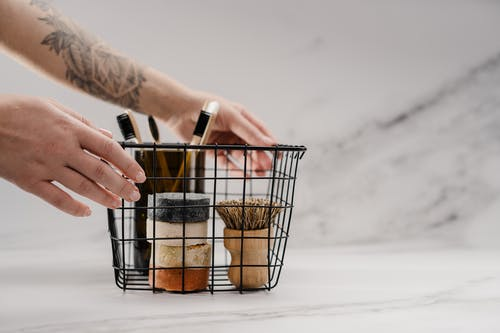 Person Holding Stainless Steel Basket With Brown and Black Metal Tools
