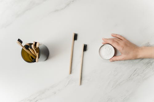 Person Holding Tooth Powder Jar Beside Bamboo Tooth Brushes