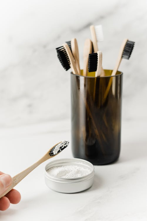 Person Holding Toothbrush With Tooth Powder Beside a Cup With Toothbrushes