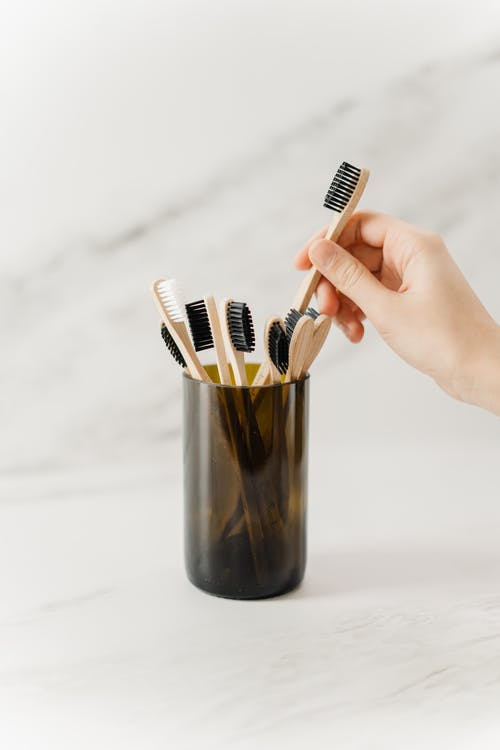 Person Holding Wooden Toothbrush