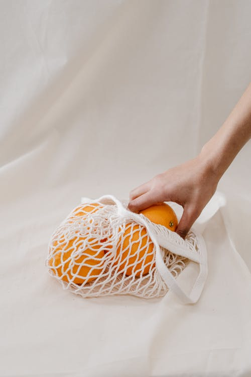 Person Holding Orange Fruit in a White Mesh Bag