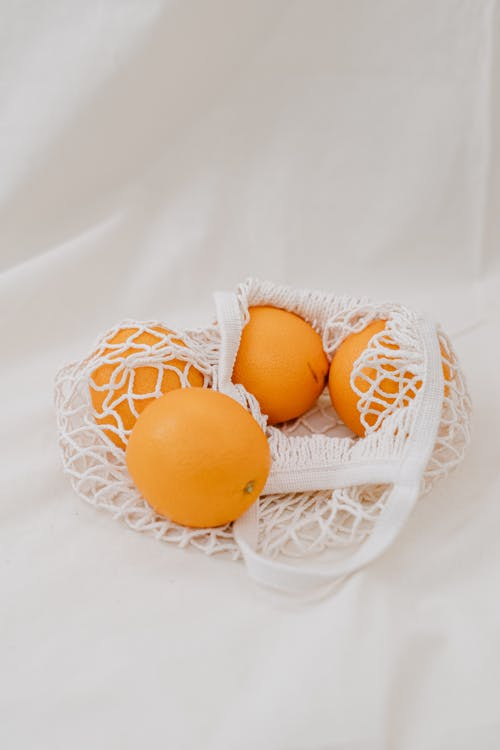 Four Yellow Oranges Eggs in White Net