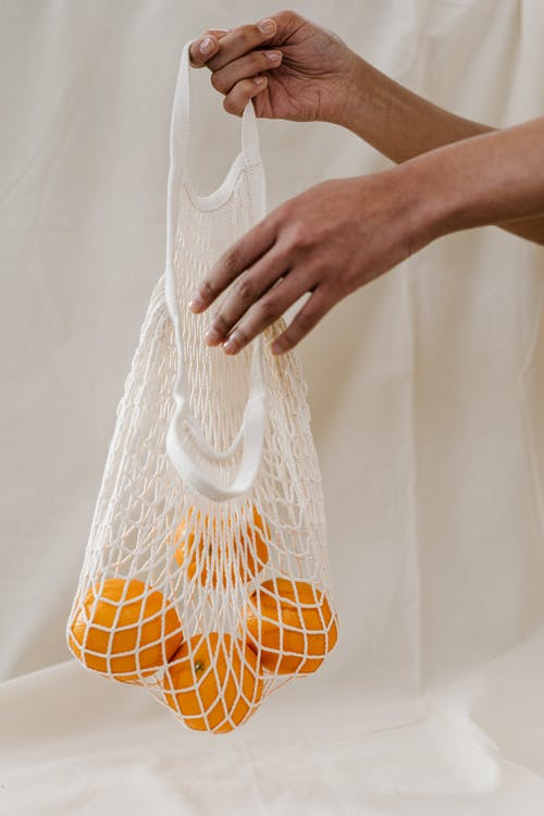 Person Holding Four Oranges in White  Net Bag