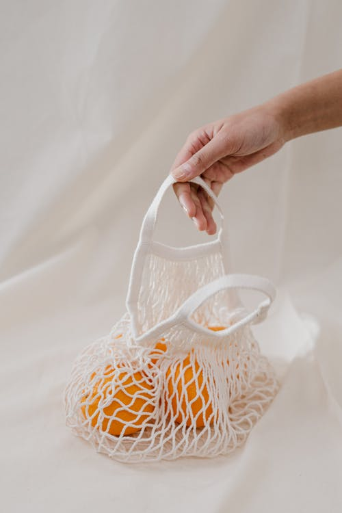 Person Holding Oranges in a White Net Bag