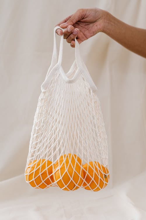 Person Holding Oranges in a White Mesh Bag