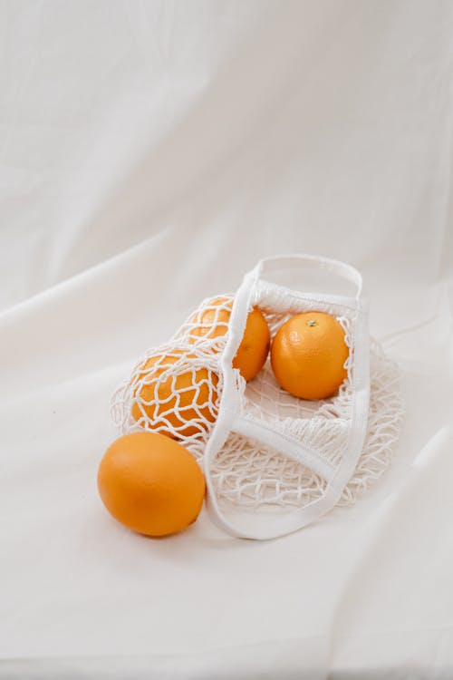 Four Orange Fruits on White Mesh Bag